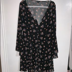 Sheer floral dress buttoned from top to bottom.